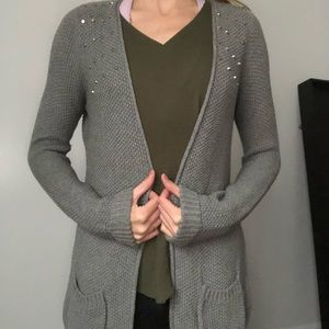 Grey knit cardigan with stud accents on shoulders
